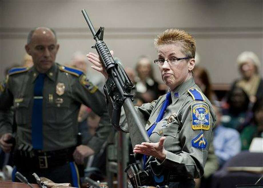 Firearms Training Unit Detective Barbara J. Mattson of the Connecticut State Police holds up a Bushmaster AR-15 rifle, the same make and model of gun used by Adam Lanza in the Sandy Hook School shooting, for a demonstration during a hearing of a legislative subcommittee reviewing gun laws, at the Legislative Office Building in Hartford, Conn., Monday, Jan. 28, 2013. The parents of children killed in the Newtown school shooting called for better enforcement of gun laws Monday at the legislative hearing. (AP Photo/Jessica Hill) Photo: AP / FR125654 AP