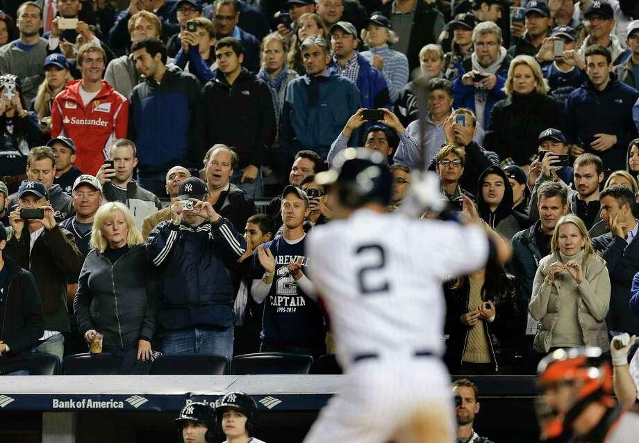 Fans stand to watch Derek Jeter bat against the Orioles on Thursday. Photo: Julie Jacobson — The Associated Press  / AP