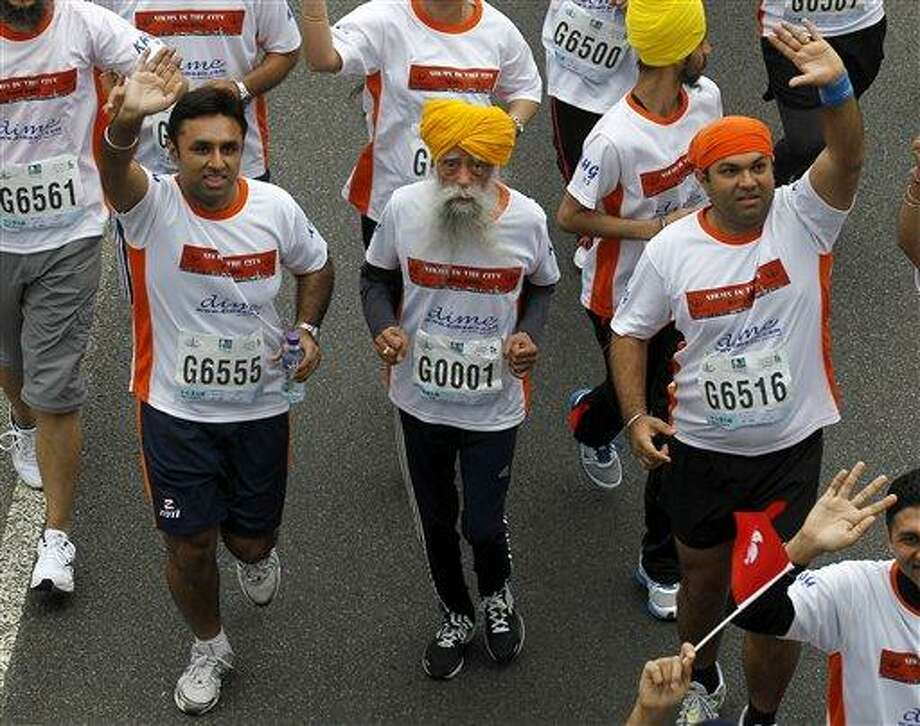 Centenarian marathon runner Fauja Singh, 101, center, originally from Beas Pind, in Jalandhar, India but who now lives in London, runs in a 10-kilometer race, part of the annual Hong Kong Marathon, in Hong Kong Sunday, Feb. 24, 2013. Singh will retire from public racing after competing in the marathon.  (AP Photo/Kin Cheung) Photo: AP / AP