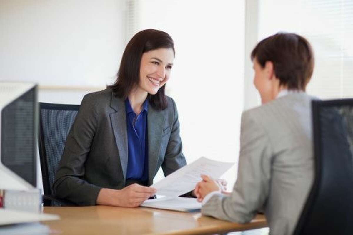 Businesswomen with paperwork talking face to face (Robert Daly)