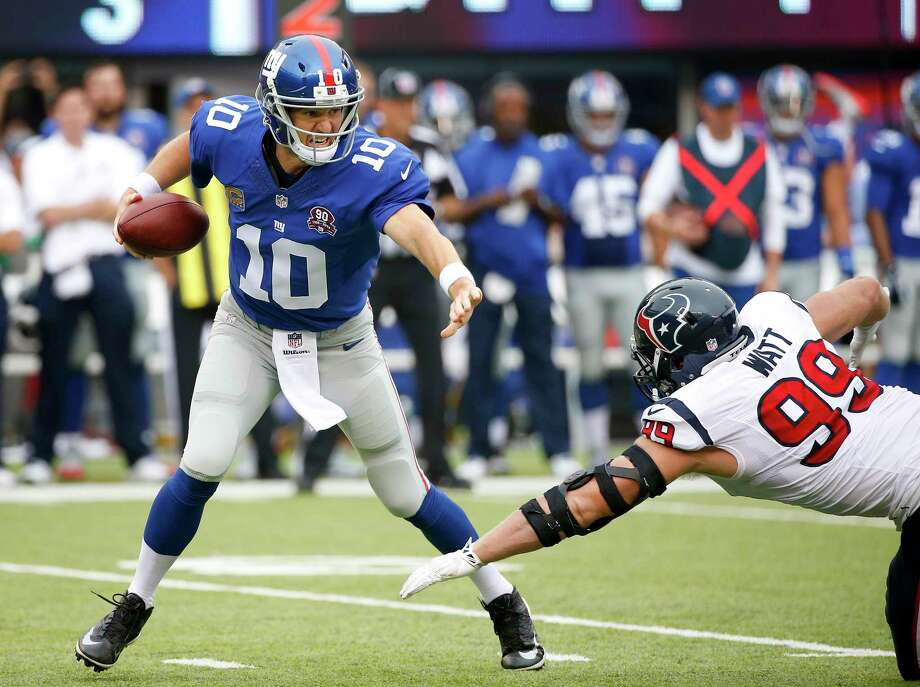 New York Giants quarterback Eli Manning tries to avoid Houston Texans defensive end J.J. Watt in the first quarter of Sunday's game in East Rutherford, N.J. Photo: Kathy Willens — The Associated Press  / AP