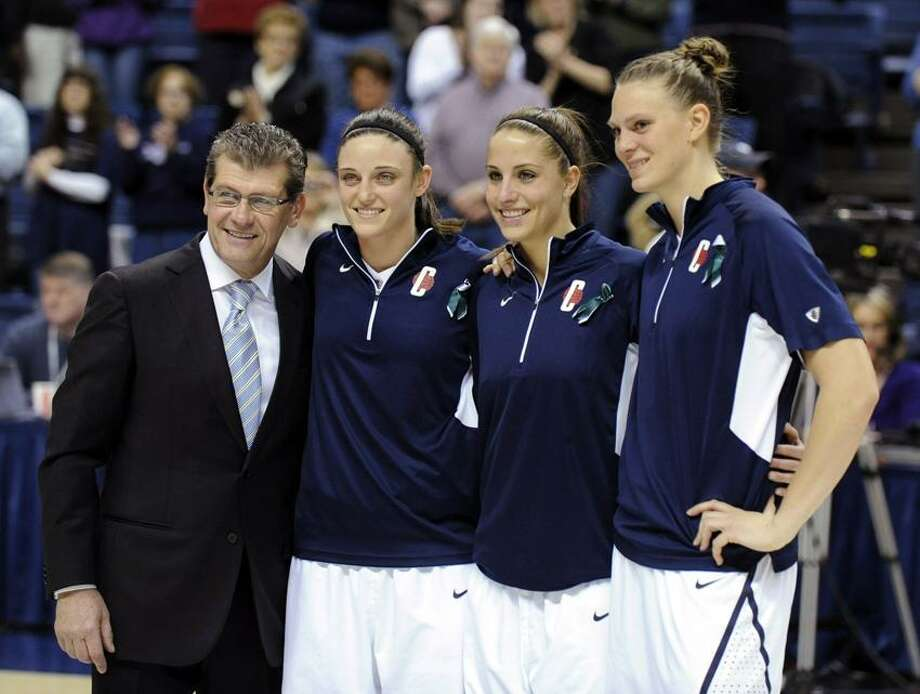 Geno Auriemma, Kelly Faris, Caroline Doty, and Heather Buck, left to right, receive awards during Senior Night ceremonies before Connecticut's NCAA basketball game against Seton Hall in Storrs, Conn., Saturday, Feb. 23, 2013. (AP Photo/Fred Beckham) Photo: AP / AP2013