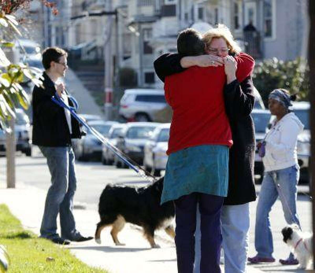 Neighbors hug outside the home of the Richard family in the Dorchester neighborhood of Boston, Tuesday, April 16, 2013. Martin Richard, 8, was killed in Mondays bombing at the finish line of the Boston Marathon.