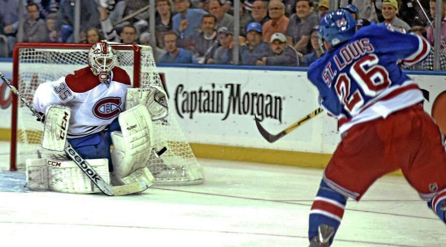 The Rangers' Martin St. Louis scores the winning goal against Montreal Canadians goalie Dustin Tokarski in overtime of Game 4 of the Eastern Conference finals on Sunday in New York. The Rangers won 3-2 and lead the best-of-seven series 3-1. Photo: Dick Druckman — The Associated Press  / DRCU