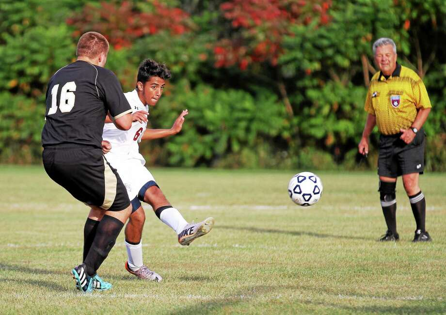 Torrington's Michael DeSousa shoots past Woodlandís Matthew Spofford to score a goal on Wednesday. Photo: Marianne Killackey — Special To Register Citizen  / 2014