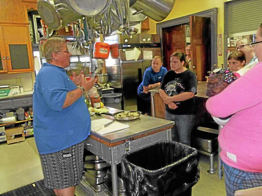 Lisa Hageman, the director of the Community Soup Kitchen, speaks to a group at the kitchen's Trinity Episcopal Church location. Photo: Jenny Golfin — Register Citizen