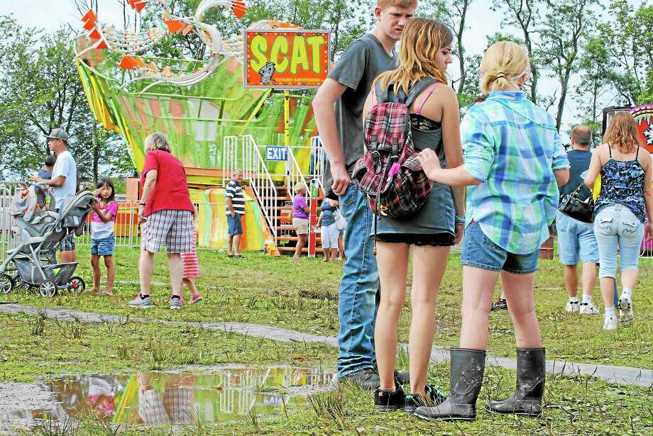 Fairgoers wore goulashes to wade through thick mud and puddles, left by Labor Day weekend storms. Photo: Journal Register Co.