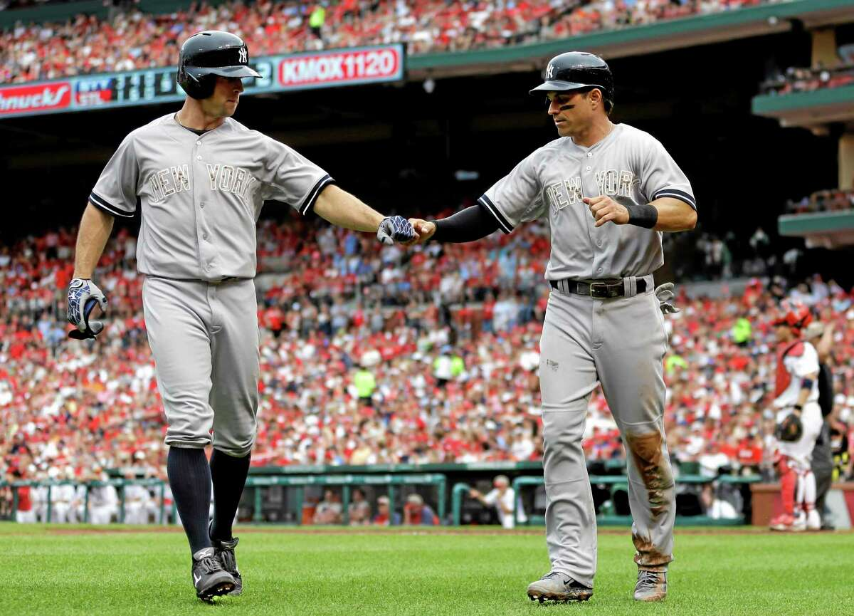 The Yankees' Brett Gardner, left, and Brian Roberts celebrate after Roberts scored on sacrifice fly by Gardner during the fifth inning Sunday.