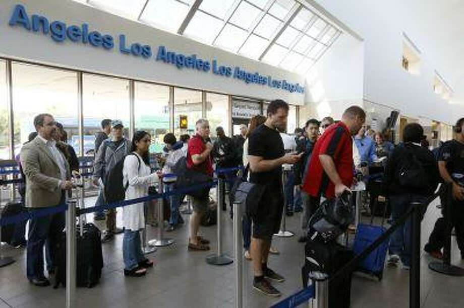 FILE - This April 22, 2013 file photo shows travelers standing in line at the LAX International Airport in Los Angeles. Under pressure, the White House signaled Wednesday it might accept legislation eliminating Federal Aviation Administration furloughs blamed for lengthy flight delays for airline passengers, while leaving the rest of $85 billion in across-the-board spending cuts in place. (AP Photo/Damian Dovarganes, File) Photo: AP / AP