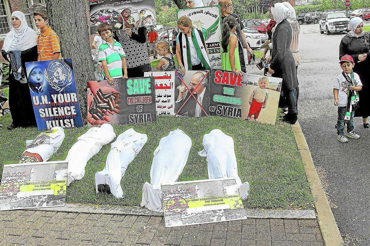 Supporters of military action in Syria outside of West Hartford Town Hall before a forum hosted by U.S. Rep. John Larson on Monday.