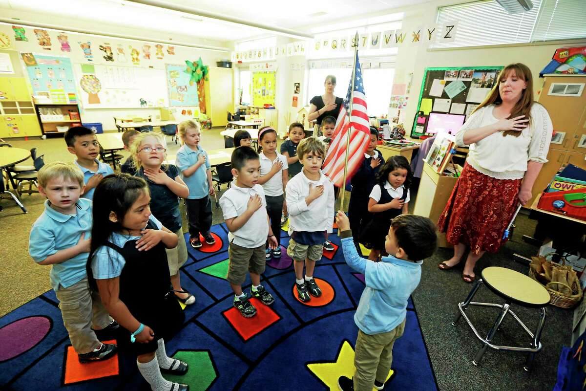 In this April 30, 2014 photo, children in Erin Kling's, right, pre-kindergarten class recite the Pledge of Allegiance at the start of the school day at Stafford Elementary School in Tacoma, Wash. The U.S. Department of Education announced in early April that Washington was losing its waiver from the restrictions of the No Child Left Behind law, which will cause state school districts to lose their say in how about $40 million in formerly flexible funding is used for education, including the formation of two pre-K classes at Stafford. (AP Photo/Ted Warren)