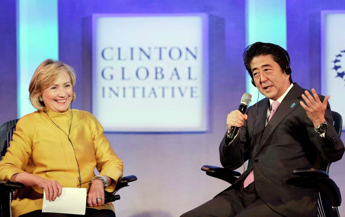 """Former U.S. Secretary of State Hillary Rodham Clinton, left, listens to Shinzo Abe, Prime Minister of Japan, during a discussion, """"Equality for Girls and Women: 2034 Instead of 2134?"""" at the Clinton Global Initiative, Wednesday, Sept. 24, 2014 in New York. (AP Photo/Mark Lennihan)"""