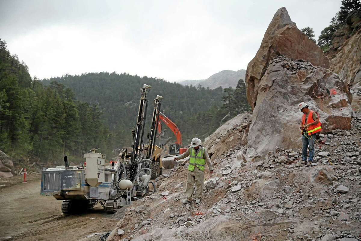 In this May 21, 2014 photo, Yenter Drilling and Blasting explosives experts Russ Yenter, left, and John Vincent string detonation cables away from blasting charges placed into holes drilled in rock, during a road-building operation on Highway 36 between Lyons at Estes Park, Colo. The goal of the project is to move the road further from the adjacent river, which undermined the road heavily during floods the previous fall, in hopes of preventing such destructive flooding in the future. (AP Photo/Brennan Linsley)
