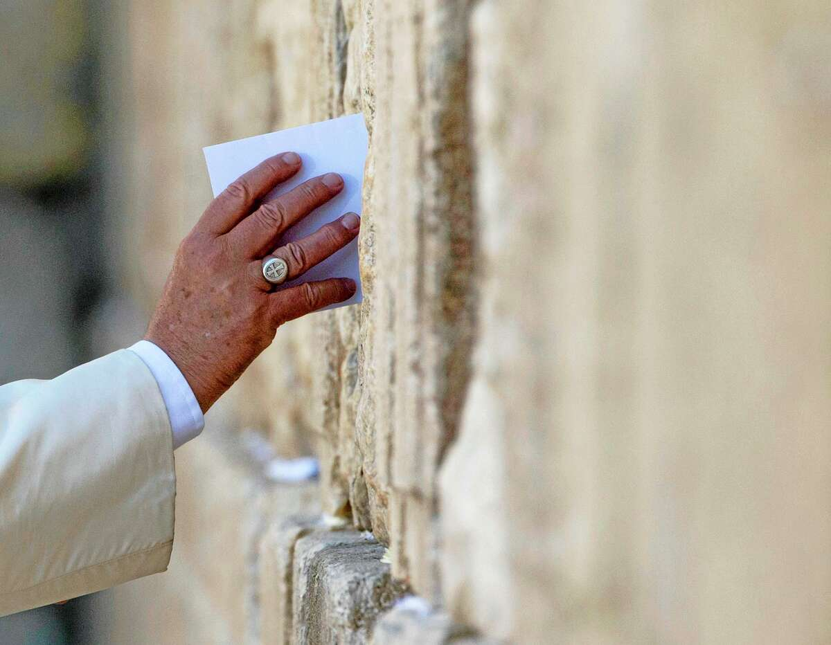 Pope Francis places an envelope Monday in one of the cracks between the stones of the Western Wall, the holiest place where Jews can pray, in the old city of Jerusalem, Israel.