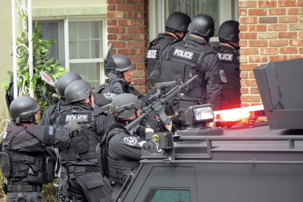 FILE - In this April 22 file phot, Nassau County police officers enter a home in Long Beach, N.Y., in search of an armed killer, based on a phone call that turned out to be a hoax.