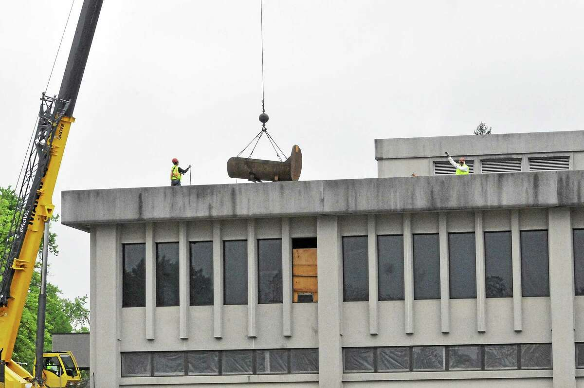 Demolition crews work on May 22 to remove pieces of a 40,300-square-foot former Torrington Company building, located at 50 Field St. The property is set to serve as a parking lot for a new $81.4 million state courthouse slate to be built in an adjacent lot.
