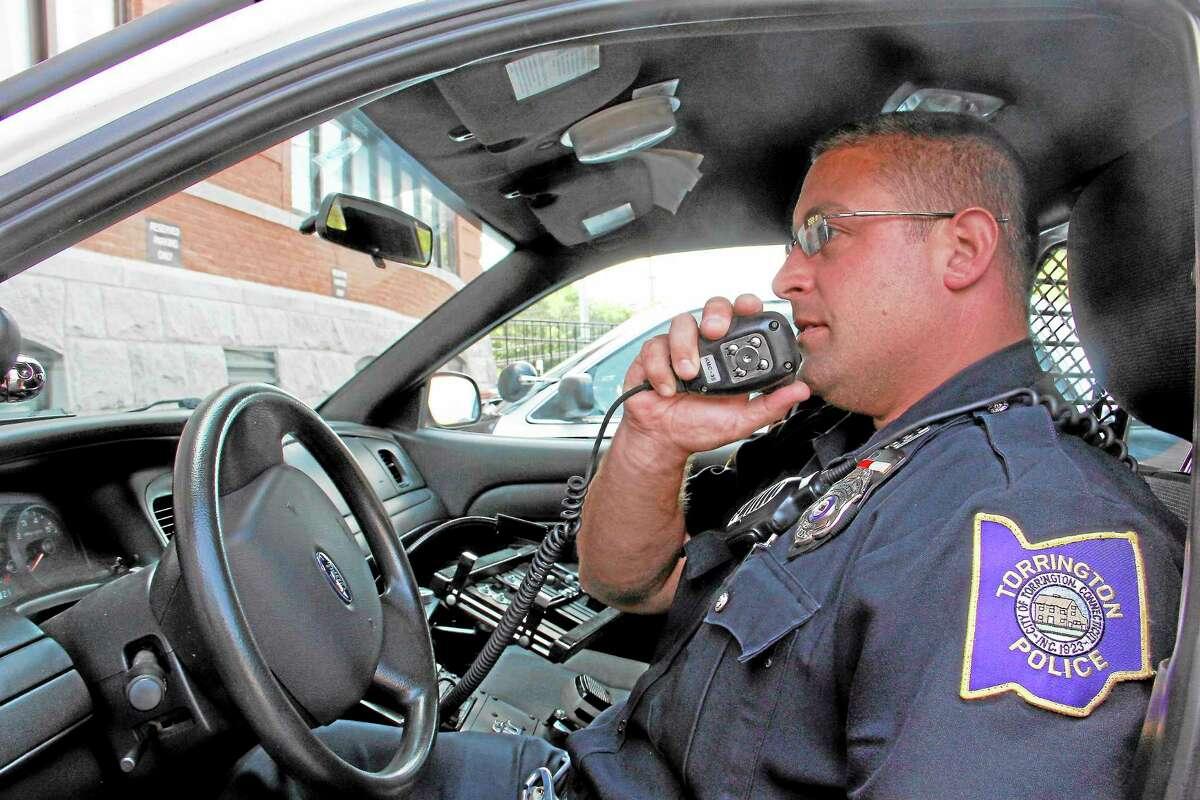 Torrington Police Department Officer William Bernabucci simulates radio communication on Friday, August 30, outside the department's headquarters. He said he's looking forward to the new radio communication system that will improve their communication.