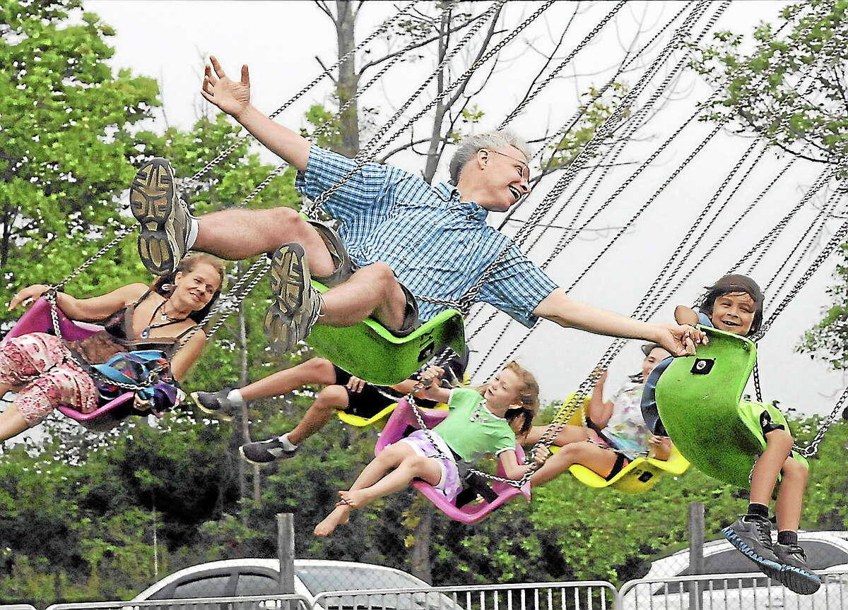 John Wardzala holds hands with his son, William, on the swings at the Goshen Fair on Saturday.