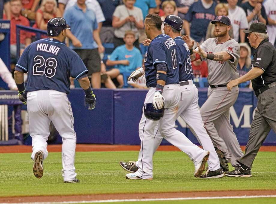 Red Sox left fielder Jonny Gomes, second right, rushes past umpire Larry Vanover, right, toward the Rays' Jose Molina (28), Yunel Escobar (11) and third base coach Tom Foley (66) in the seventh inning Sunday. Photo: Steve Nesius — The Associated Press  / FR69810 AP