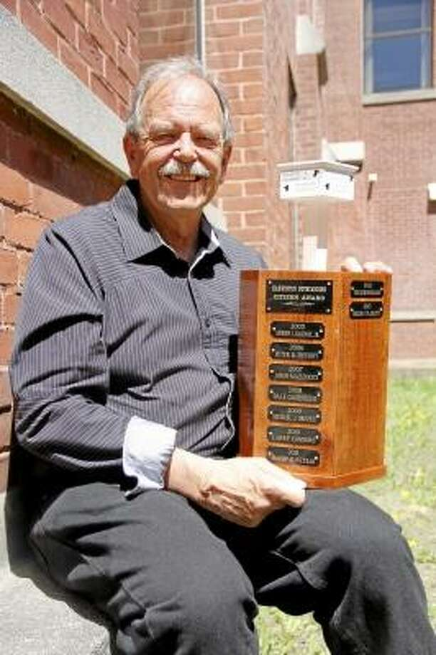 Roger P. Plaskett poses with the Harwinton Outstanding Citizen Award on Wednesday, May 1, 2013 in Torrington. Plaskett was named the 2013 recipient of the award in February, and had a banquet in his honor on April 26. The award is hand-crafted from Harwinton cherry wood and was designed by 2010 winner Larry Connors. It's the second incarnation of the award after the first one, which was first handed in 1975, filled up. (ESTEBAN L. HERNANDEZ/REGISTER CITIZEN)