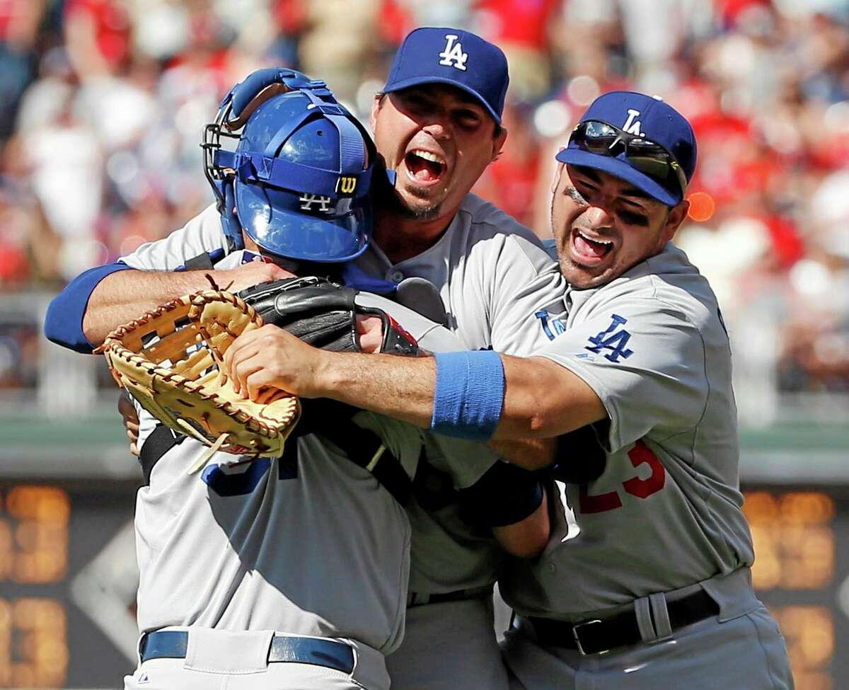 Dodgers starting pitcher Josh Beckett, center, celebrates with catcher Drew Butera, left, and first baseman Adrian Gonzalez after pitching a no-hitter Sunday.