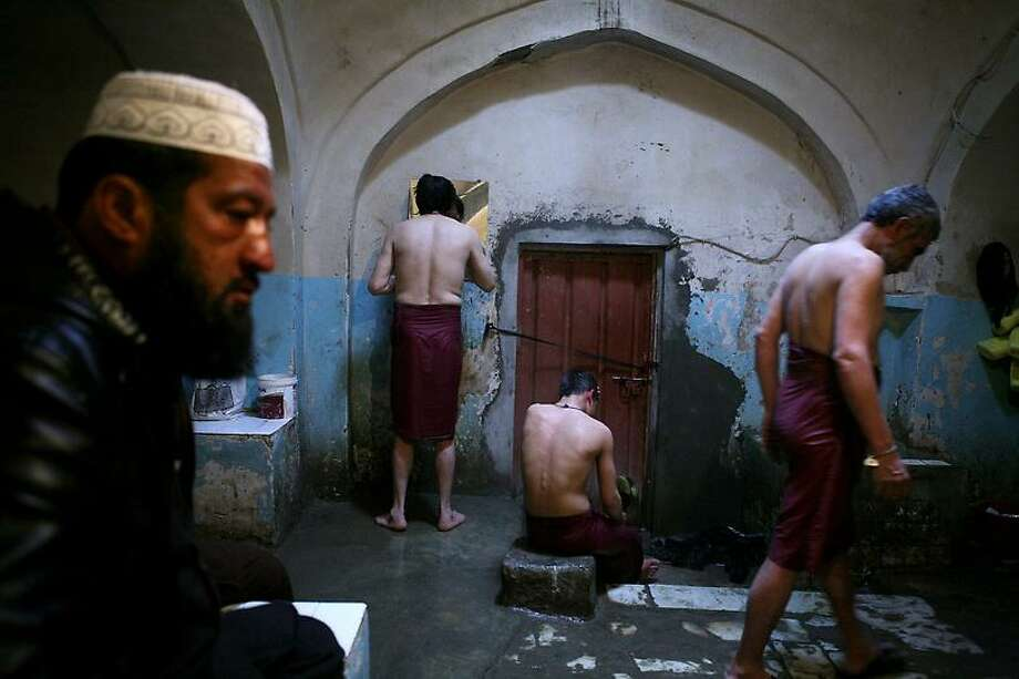 Afghan men gather in a Hamam, or public bath in Kabul, Afghanistan, on Thursday, Feb. 21, 2013. The public baths are thought to originate from Turkey, and are found in the big cities of Afghanistan where they are mostly used by poor people, who after decades of war, most do not have access to hot or cold running water in their homes. (AP Photo/Ali Hamed Haghdoust) Photo: ASSOCIATED PRESS / AP2013