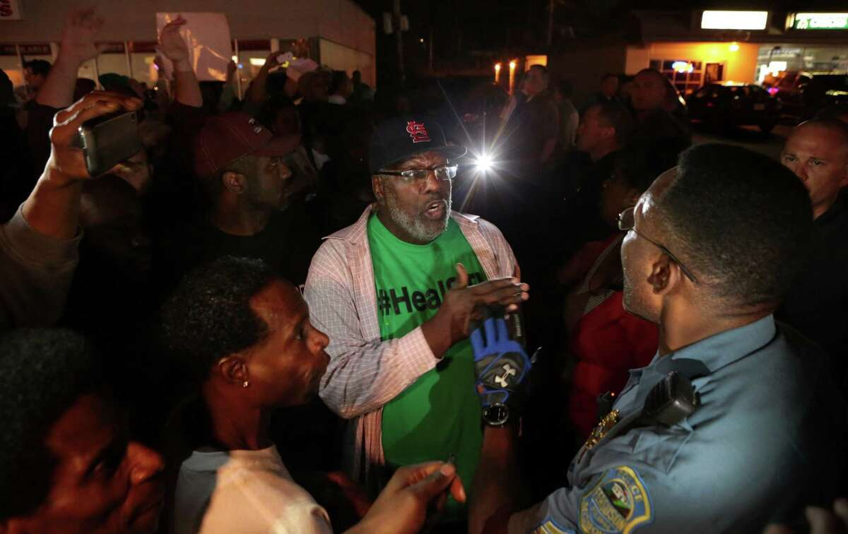 Protesters argue with a Ferguson sergeant who was trying to get them to disperse the area on West Florissant Avenue in Ferguson late Tuesday, Sept. 23, 2014.