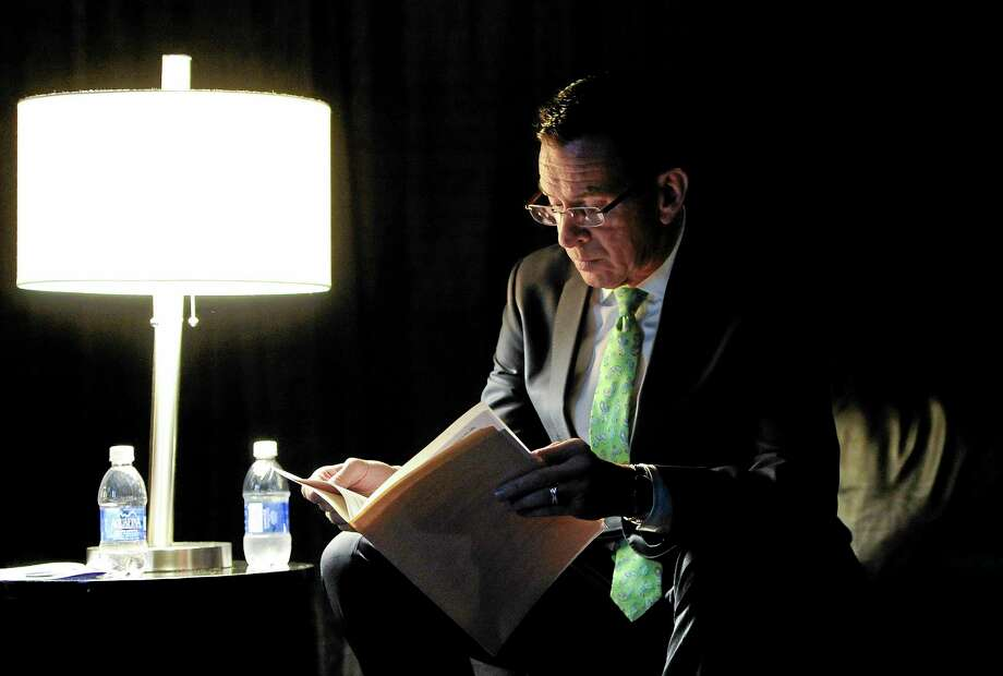 Gov. Dannel P. Malloy reads over his speech in a private area backstage while waiting as delegates nominate him as the Democratic candidate for governor at the Connecticut Democratic Convention, Friday, May 16, 2014, in Hartford, Conn. (AP Photo/Jessica Hill) Photo: AP / FR125654 AP
