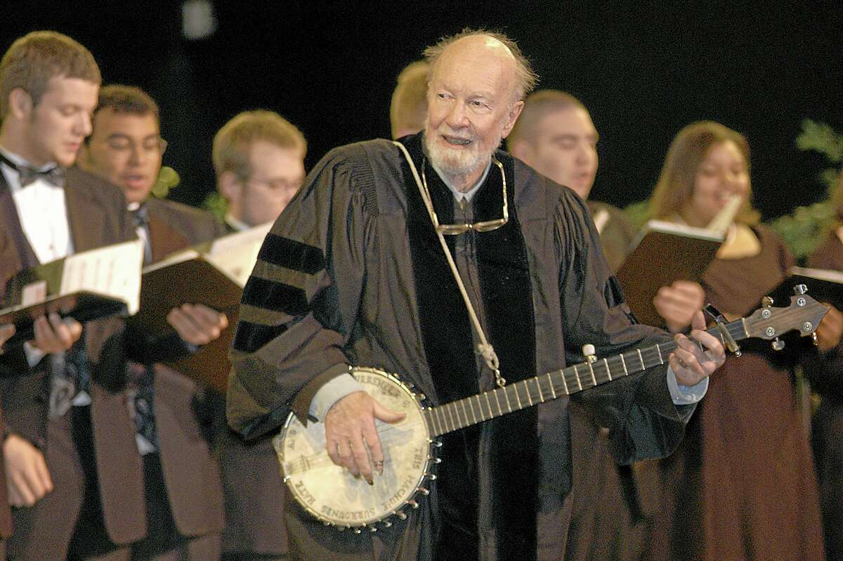 """File-This May 10, 2003 file photo shows folk singer Pete Seeger performing""""When the Saints Go Marching In"""" with the Saint Rose Chamber Singers during commencement ceremonies for the College of St. Rose at the Empire State Plaza in Albany, N.Y. The American troubadour, folk singer and activist Seeger died Monday Jan. 27, 2014, at age 94. (AP Photo/Stewart Cairns, File)"""