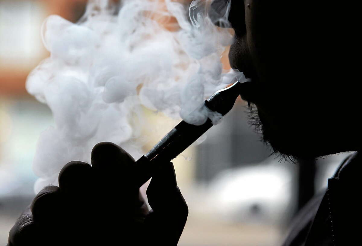 An electronic cigarette is demonstrated in Chicago. Some makers of the liquid nicotine used in electronic cigarettes are using notable brand names like Thin Mint, Tootsie Roll and Cinnamon Toast Crunch to sell their wares.