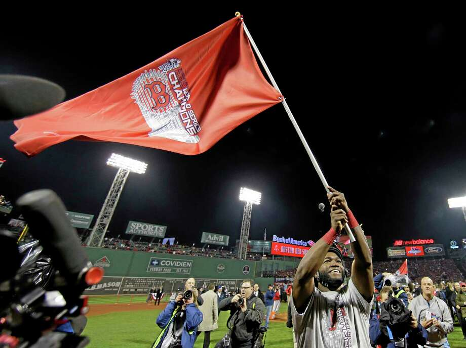 Red Sox designated hitter David Ortiz waves a flag after Boston defeated the St. Louis Cardinals in Game 6 of the World Series Wednesday at Fenway Park. Photo: Matt Slocum — The Associated Press  / AP