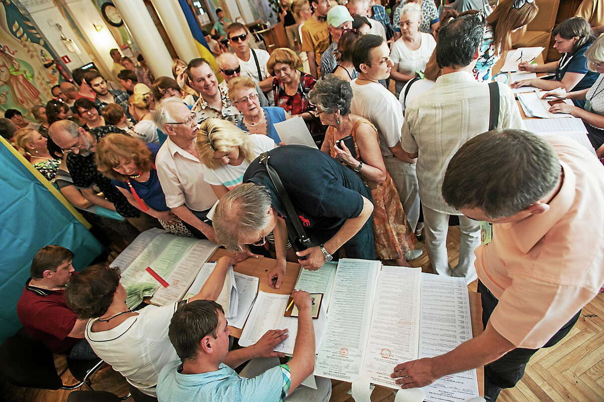 Ukrainians stand in line to receive their ballots at a polling station during presidential and mayoral elections in Kiev, Ukraine, Sunday, May 25, 2014.