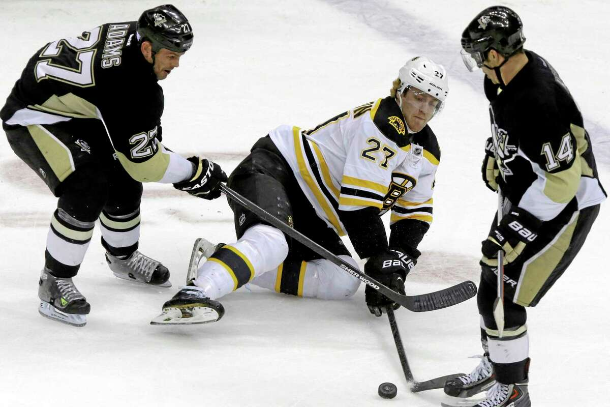 The Bruins' Dougie Hamilton (27) reaches for the puck after being checked to the ice by the Penguins' Craig Adams (27) during the third period of Wednesday's game in Pittsburgh. The Penguins won 3-2.