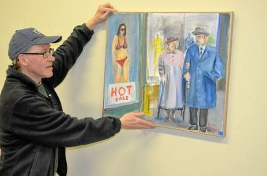 Michael Yurgeles, Artwell executive director, hung artwork in preparation for the More Amore exhibit opening Saturday night. Kate Hartman/Register Citizen.