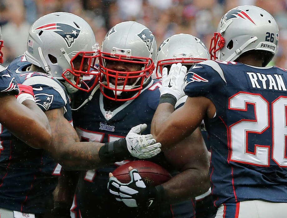 New England Patriots defensive tackle Dominique Easley, left, and cornerback Logan Ryan (26) celebrate with defensive tackle Vince Wilfork, center, after his interception in the fourth quarter of Sunday's game against the Oakland Raiders in Foxborough, Mass. Photo: Elise Amendola — The Associated Press  / AP