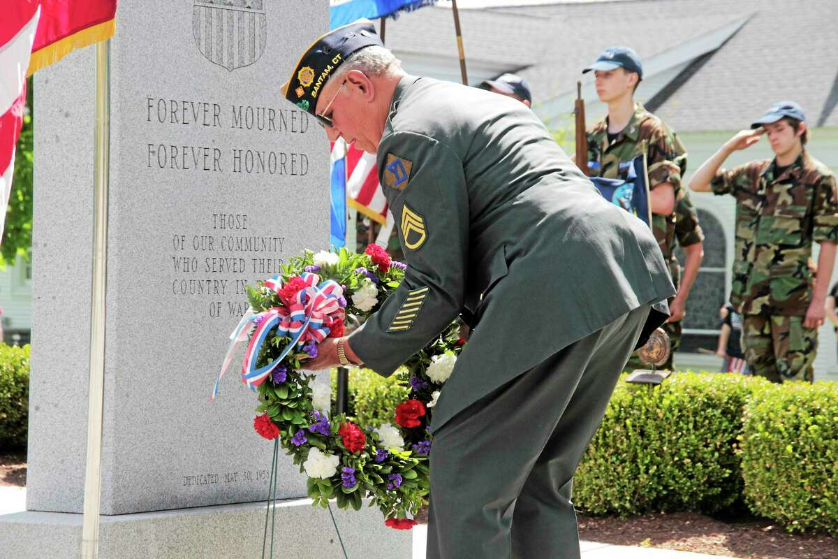 A wreath is placed on the All Wars Memorial in Bantam during the town's Memorial Day Parade Sunday.