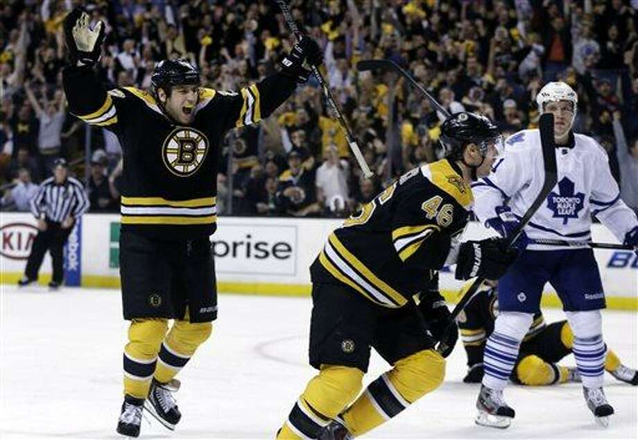 Boston Bruins left wing Milan Lucic, left, celebrates a goal scored by center David Krejci (46) as Toronto Maple Leafs left wing Nikolai Kulemin (41) looks on during the second period in Game 1 of a first-round NHL hockey playoff series in Boston, Wednesday, May 1, 2013. (AP Photo/Elise Amendola) Photo: AP / AP