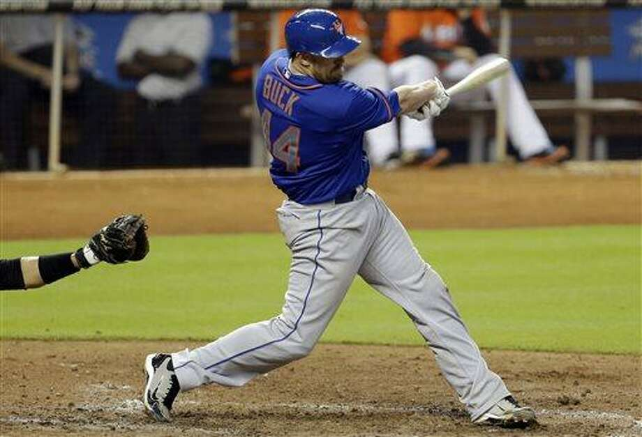 New York Mets' John Buck hits an RBI double to score two runs in the seventh inning of a baseball game against the Miami Marlins, Wednesday, May 1, 2013, in Miami. The Mets won 7-6.(AP Photo/Lynne Sladky) Photo: AP / AP