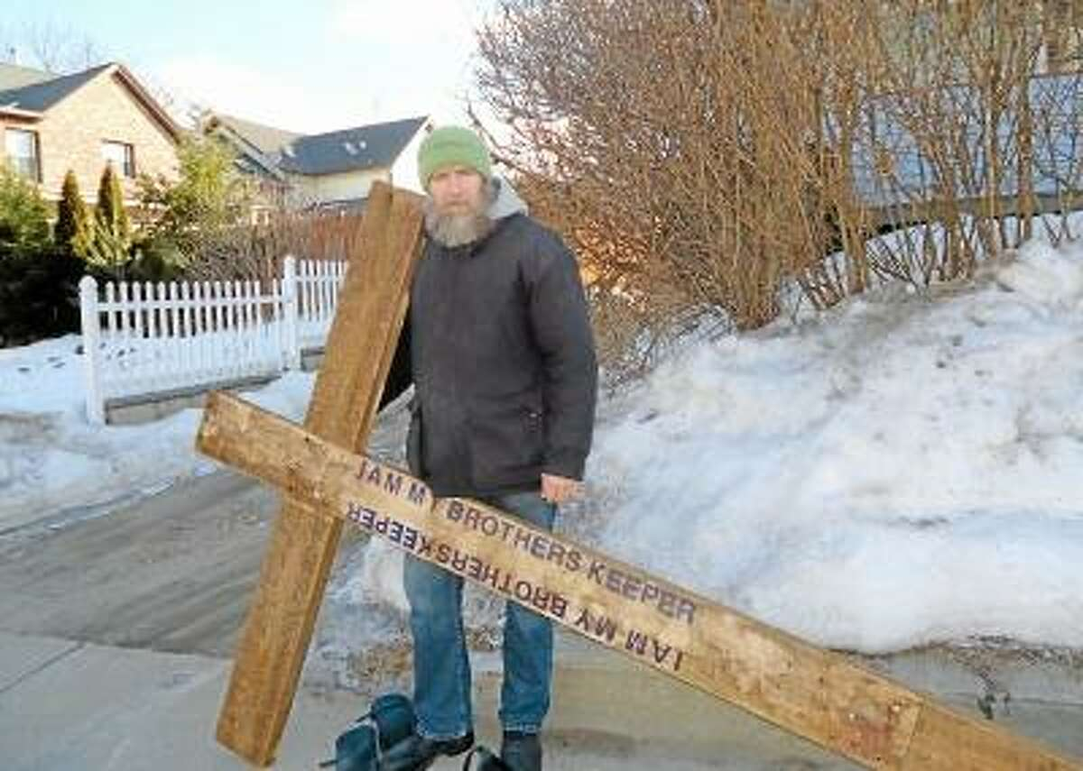 John Schweppe, a local homeless man carrying the cross on his daily trek from FISH to Primetime House. Jenny Golfin/Register Citizen.
