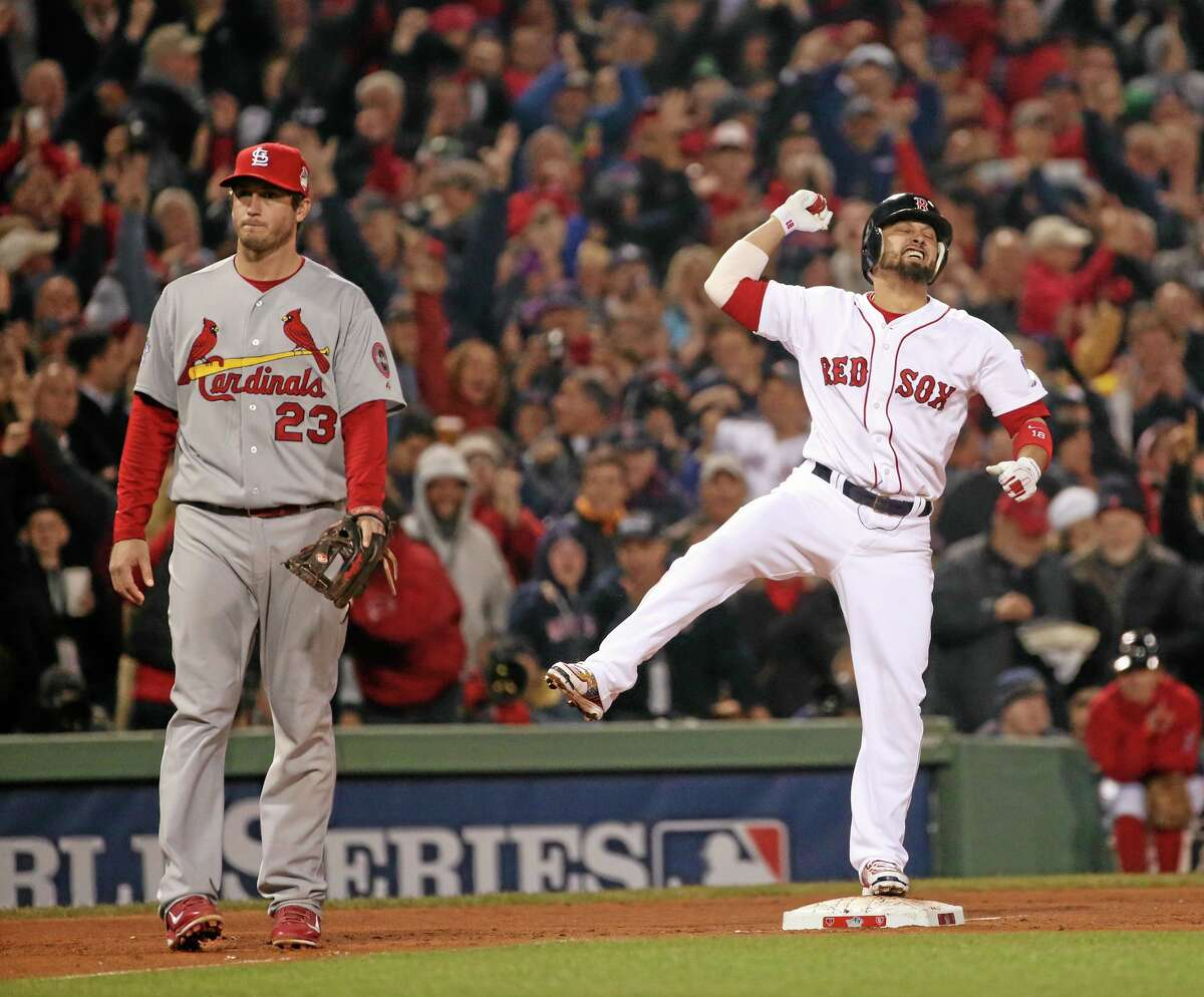 The Red Sox's Shane Victorino reacts after his three-run double in the third inning of Game 6 of the World Series against the St. Louis Cardinals on Wednesday night at Fenway Park in Boston. Cardinals third baseman David Freese looks on. The Red Sox won 6-1 to win the Series.
