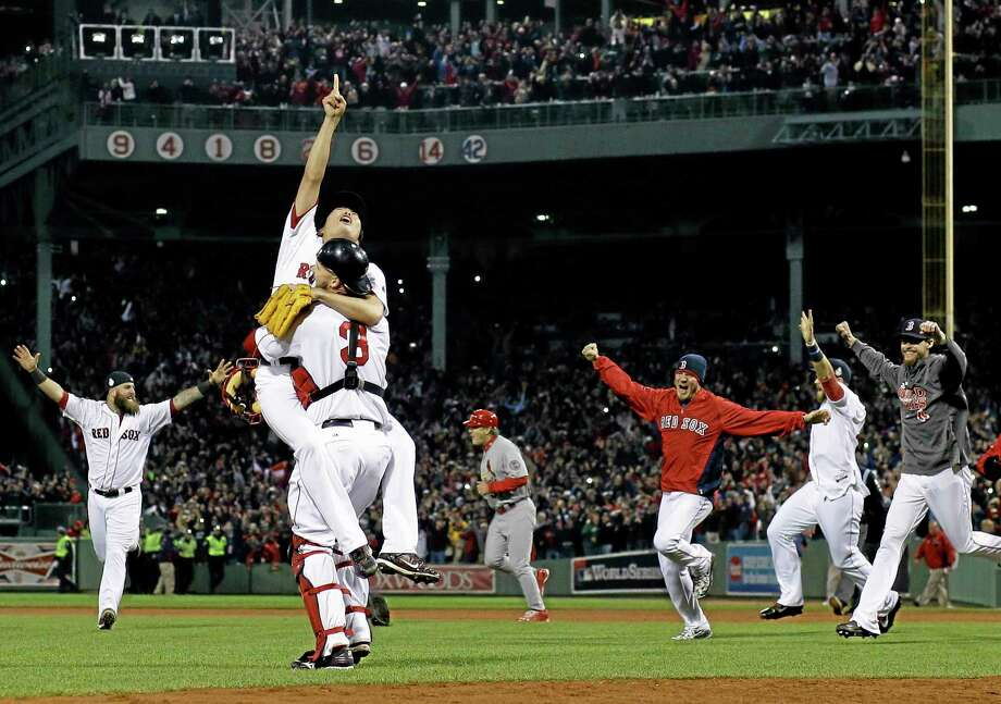 Red Sox relief pitcher Koji Uehara and catcher David Ross celebrate after getting the St. Louis Cardinals' Matt Carpenter to strike out and end Game 6 of the World Series Wednesday in Boston. The Red Sox won 6-1 to win the Series. Photo: Matt Slocum — The Associated Press  / AP