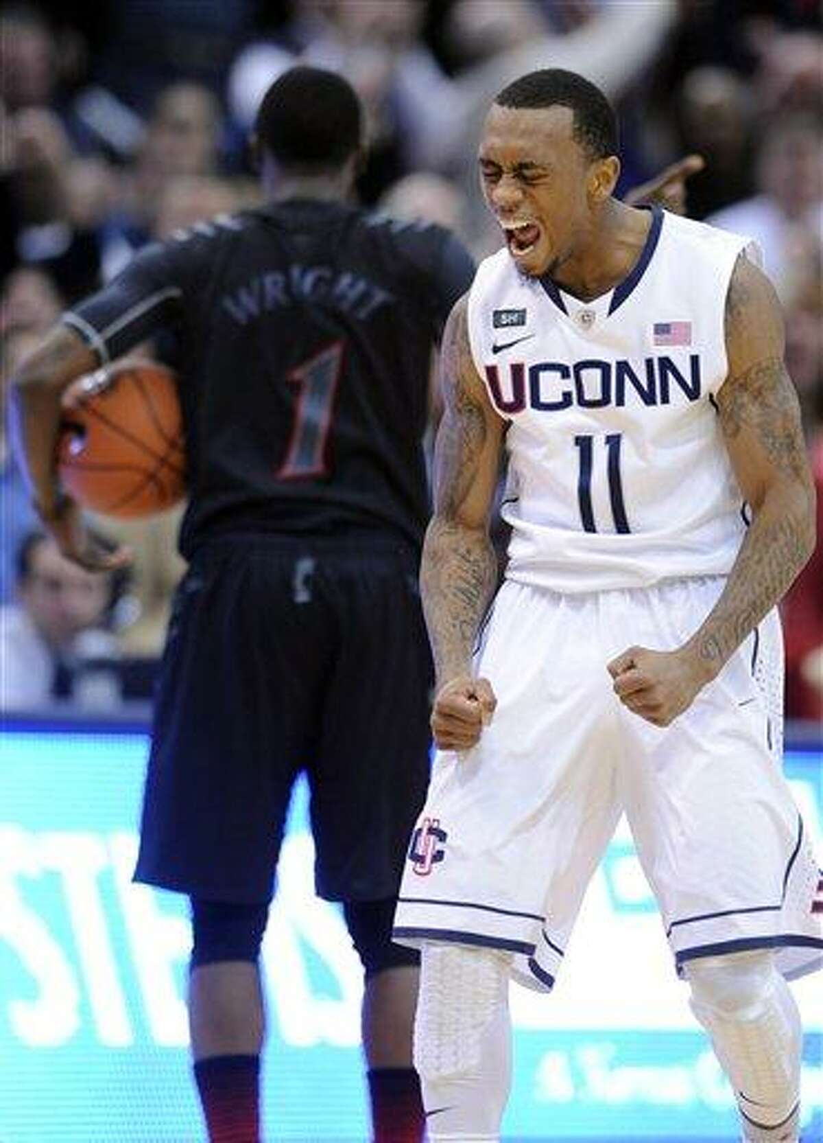 Connecticut's Ryan Boatright, right, celebrates after Cincinnati's Cashmere Wright, background, turned the ball over late in overtime of Connecticut's 73-66 victory in an NCAA college basketball game in Hartford, Conn., Thursday, Feb. 21, 2013. (AP Photo/Fred Beckham)