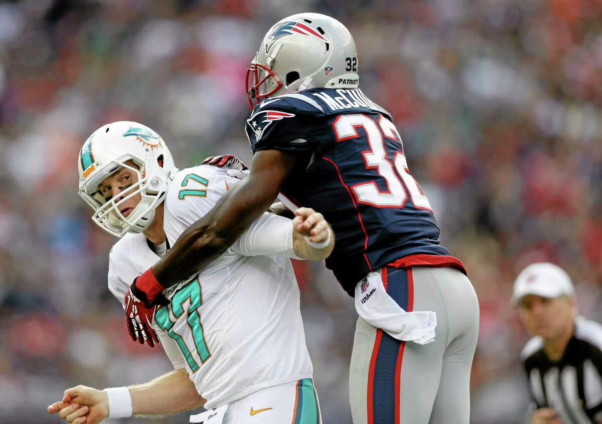 New England Patriots free safety Devin McCourty (32) grabs Miami Dolphins quarterback Ryan Tannehill during the first quarter of Sunday's game in Foxborough, Mass.