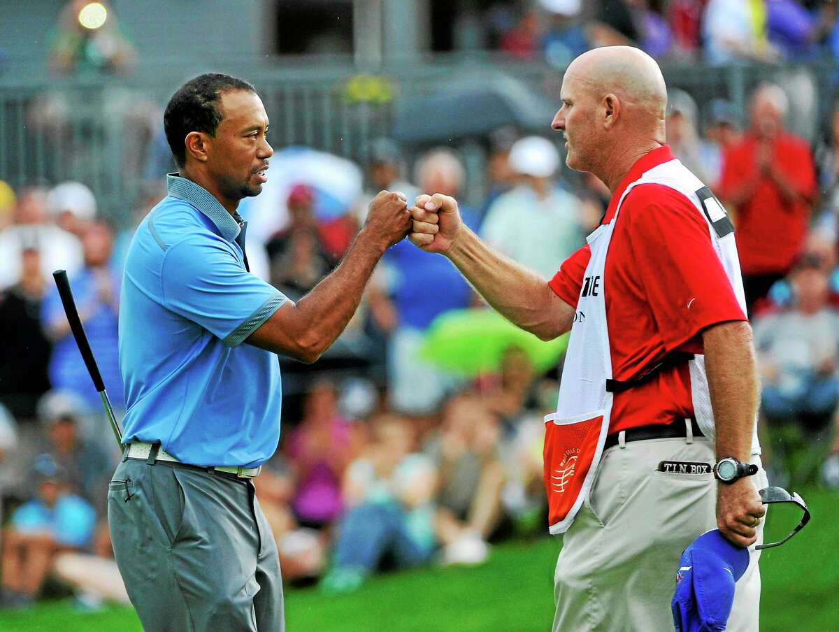 Tiger Woods celebrates with his caddie, Joe LaCava, after finishing his second round at the WGC Bridgestone Invitational last August.