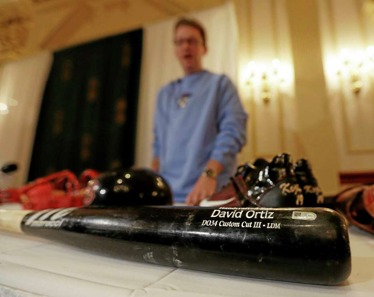 Brad Horn of the Baseball Hall of Fame displays a bat used by Boston Red Sox designated hitter David Ortiz in the World Series during a news conference on Thursday in Colonie, N.Y. Items from the series are headed to Cooperstown and will be on display in the Hall's Autumn Glory exhibit. The Red Sox won the series by defeating the St. Louis Cardinals in six games.