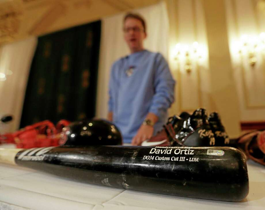 Brad Horn of the Baseball Hall of Fame displays a bat used by Boston Red Sox designated hitter David Ortiz in the World Series during a news conference on Thursday in Colonie, N.Y. Items from the series are headed to Cooperstown and will be on display in the Hall's Autumn Glory exhibit. The Red Sox won the series by defeating the St. Louis Cardinals in six games. Photo: Mike Groll — The Associated Press  / AP