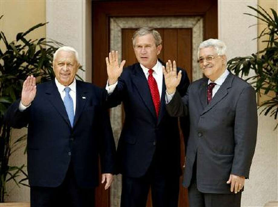 Former President George W. Bush, center, with Israel's former Prime Minister Ariel Sharon, left, and Palestinian Prime Minister Mahmoud Abbas, in a 2003 file photo. Photo: AP / AP