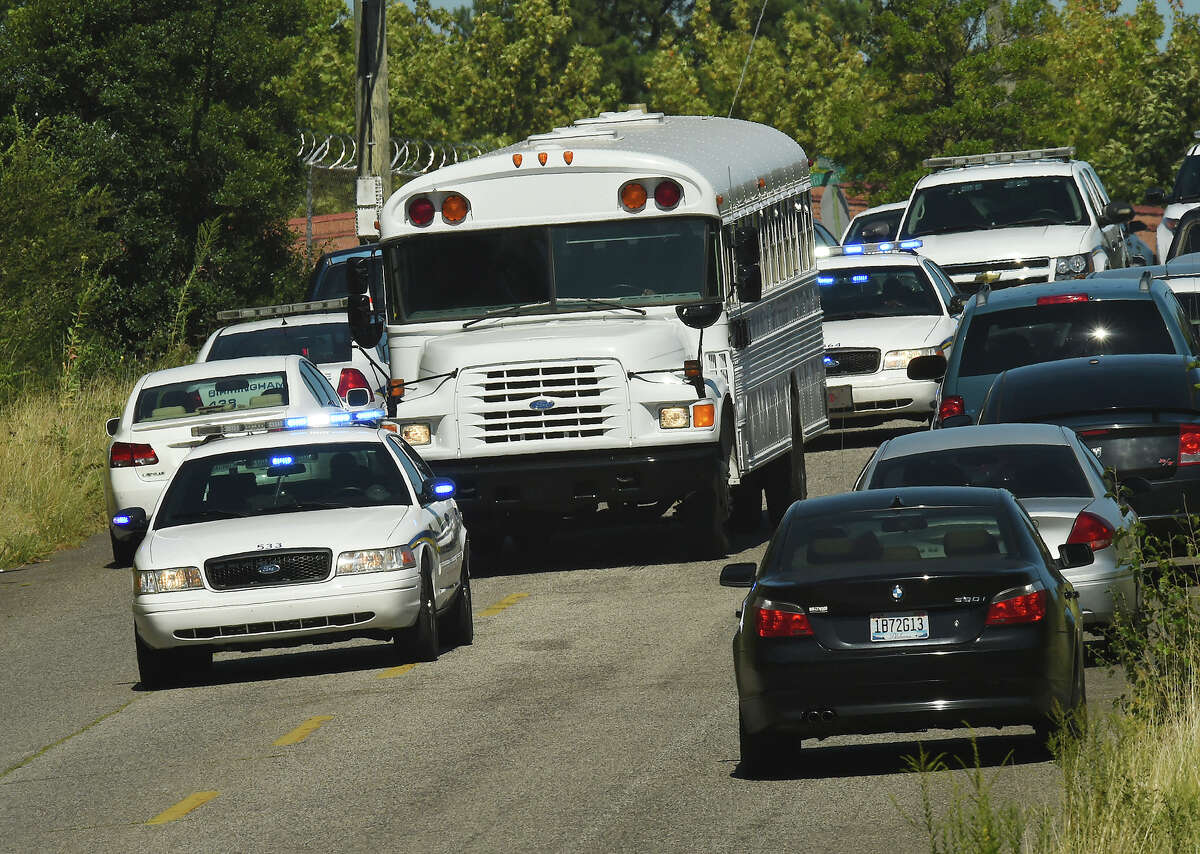 Police officers escort UPS employees on a bus from the scene where three people were killed, including the gunman, at a UPS facility in Birmingham, Ala., Tuesday, Sept. 23, 2014.