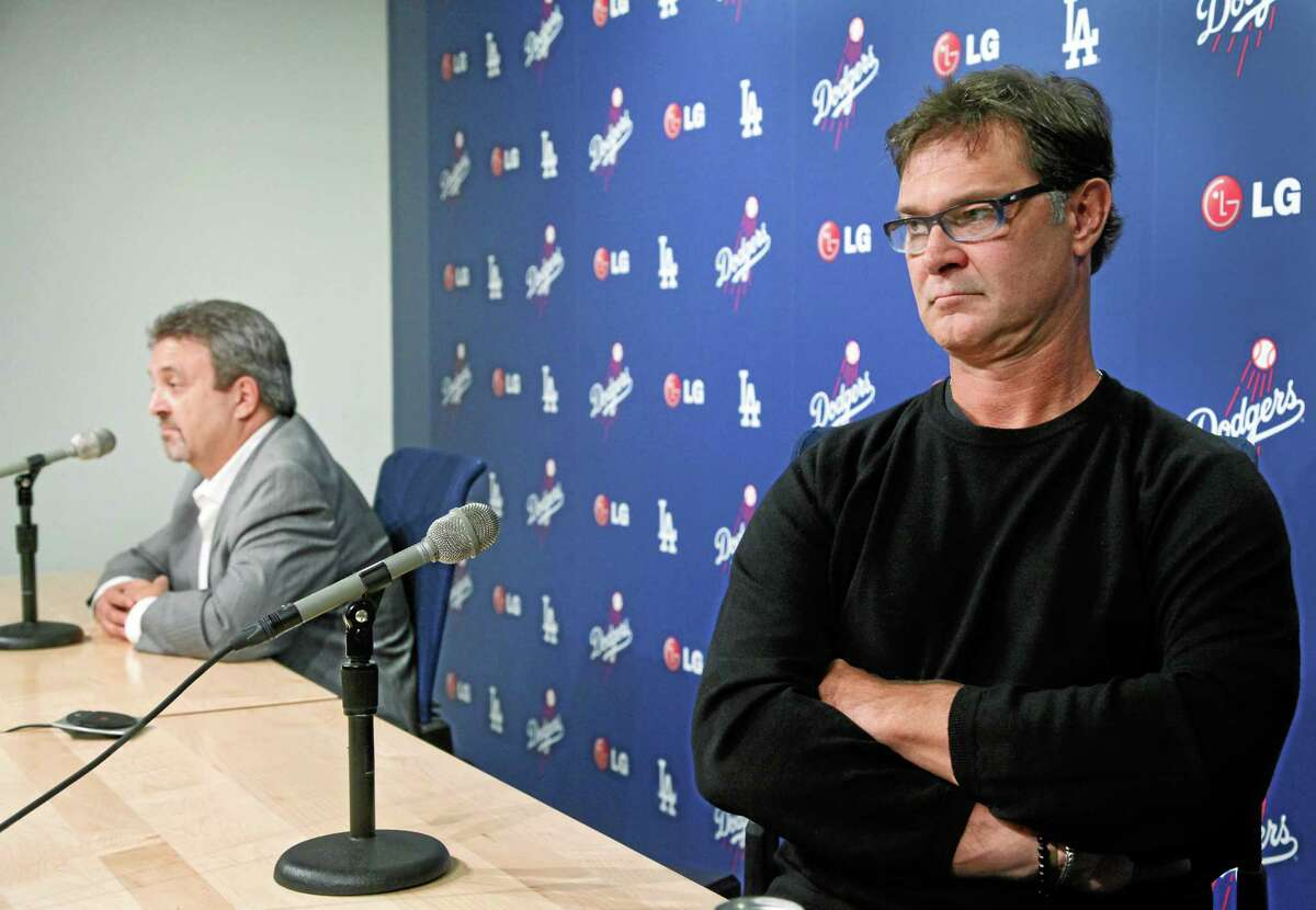Los Angeles general manager Ned Colletti, left, manager Don Mattingly and the Dodgers are favorites to win the 2014 World Series.