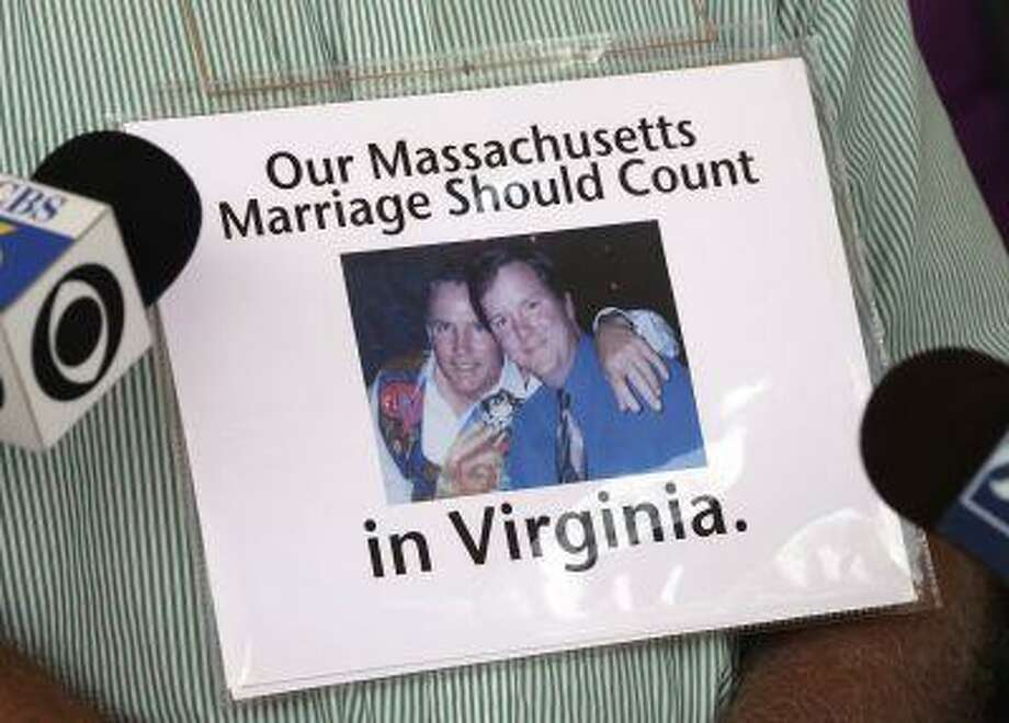 Judd Proctor wears a sign with a photo of himself and his partner during a press conference concerning the U.S. Supreme court's decision on the Defense of Marriage law in Richmond, Va., Wednesday, June 26, 2013. Photo: ASSOCIATED PRESS / AP2013